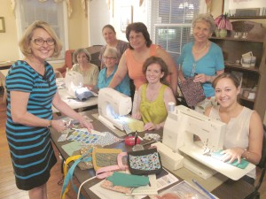 Participating in a sewing bee at the Langford-Nord House in Blythewood to sew purses for school girls in Zambia are organizer Kem Smith, Gail Corn, Lynne Richardson, Frankie McLean (seated), Vivian Bickley, Lisa Smith, Jeanette Smith and Caroline Burgos. The women, who brought their portable sewing machines, produced nine purses during the bee.