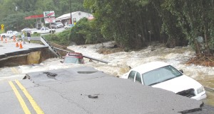 A pair of vehicles plunged into the raging waters Sunday as a 20-foot section of Highway 21 near Lake Elizabeth collapsed under their wheels. The occupants were rescued as the record breaking storm changed the landscape of the Midlands. (Photo/Barbara Ball)