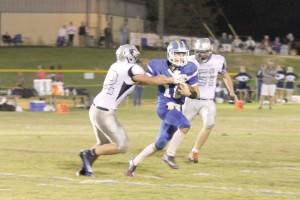 RWA quarterback Gunnar Hensley feels the pressure of the Greenwood Christian defense. (Photo/Martha Ladd)