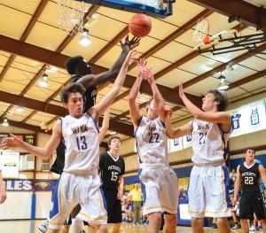 Noah Edwards (13), Mitchell Gibbons (22) and Gunnar Hensley (21) do battle under the basket. (Photo/Ross Burton)