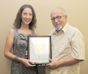 Bill Rogers, Executive Director of the S.C. Press Association (right) presents Voice graphic designer Ashley Ghere with her fifth consecutive Best in Show PALMY Award for ad design.