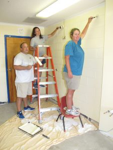 Volunteer painters Jeff and Allison Spires and Rhetta Taylor put the finishing touches on a classroom at Richard Winn Academy. (Photo/Barbara Ball)