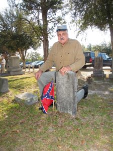 Dressed as a Confederate Soldier, Fritz Jolly kneels beside the grave of Drummer Boy William Woodward Macon who is interred under a shade tree in the Sandy Level Baptist Church. (Photo/Barbara Ball)