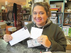 """Liz Humphries, owner of Blythewood Consignment Shop on Main Street in Blythewood, recently loaned a stranger $5 for fuel for his pickup truck. """"And then,"""" she said, """"to my surprise, I got this!"""" (Photo/Barbara Ball)"""