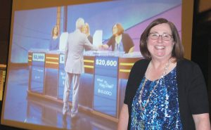 During a watch night party at Columbia Country Club, Dr. Cheryl Guy, Principal of Westwood High School, stands next to a big screen showing Jeopardy host Alex Trebek congratulating her on her big win on the show Friday night. (Photo/Barbara Ball)