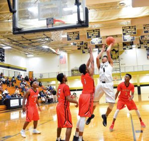 Fairfield Central's Chandon Davis (1) puts up a shot surrounded by Redhawks Russell Jones (2), Xavier Dobey (5), Terrance Barnes (1) and Terrell Harris (3). (Photo/Joe Seibles)