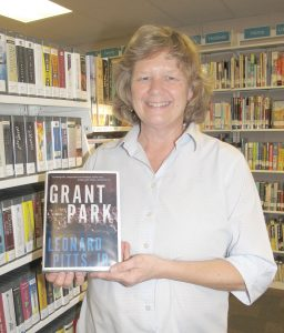 Fiona Smith, Library Associate at the Blythewood Library, holds a copy of 'Grant Park,' a thirller about racial tensions and the subject of the community's second Blythewood Reads event to be held in February. (Photo/Barbara Ball)