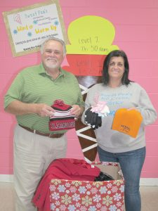 Blythewood Mayor J. Michael Ross and Susan DeMarco, owner of Sweet Pea's Ice Cream in Blythewood, display some of the warm weather jackets, hats and gloves that have been donated for homeless people in the community. (Photo/Barbara Ball)